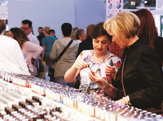 <p>At Beauty Düsseldorf, two attendees admire a classic red polish.</p>