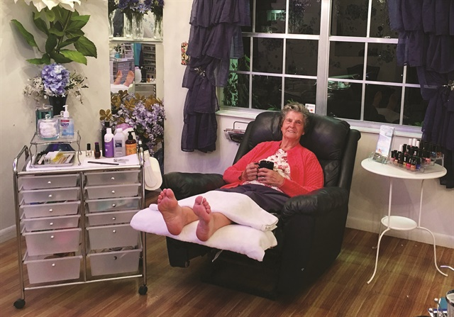 <p>Client Carol relaxes in an overstuffed recliner that is used as a pedicure chair at Z-Hills.</p>