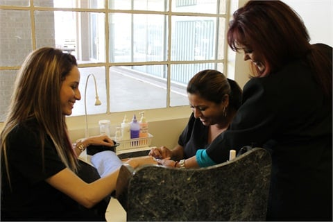 <p>San Antonio School Director, Mrs. Cantu, inspects the work preformed by Nail Techs, Patricia Castillo and Maria Perez.</p>