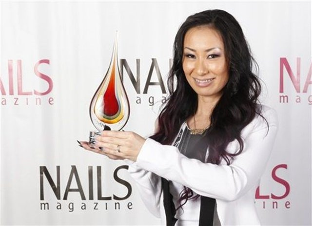 Ryoko Garcia proudly displays her NAILS Next Top Nail Artist trophy.