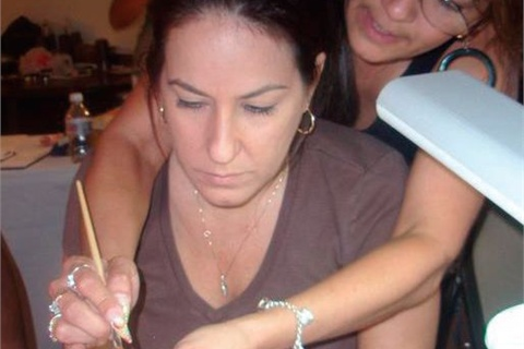 <p>The HRTE founder Tammy Warner gets hands on in showing an attendee how to do acrylic pink-and-whites.</p>