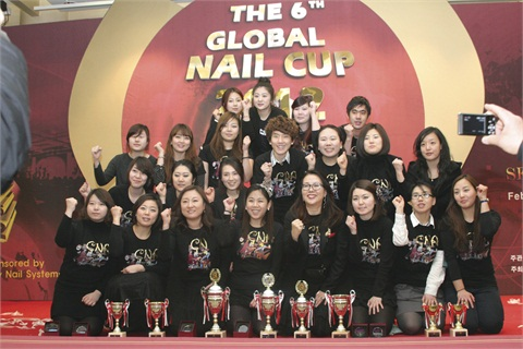 "<p>The many members of the Choi Kyung Hee Nail Academy show off their ""fighting spirit"" with determined fists and smiles.</p>"