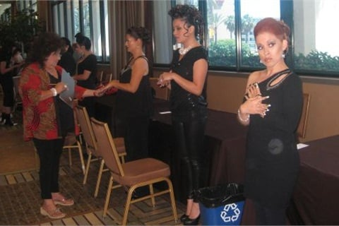 A judge analyzes nails done by students at the Barristar Beauty School Forum. The competition is broken into parts — nails, make-up, and hair — with each part being judged separately, plus a team score is given for the whole package.