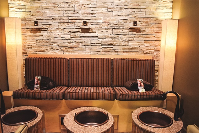 A compact but ultra-luxurious pedicure bench for three was added to Breanna Herriott's complete salon remodel at Breeze Salon & Spa. The space features a dramatic stone wall with candle sconces, diffused light from two fabric Japanese torchieres, and round pedicure basins topped with granite.