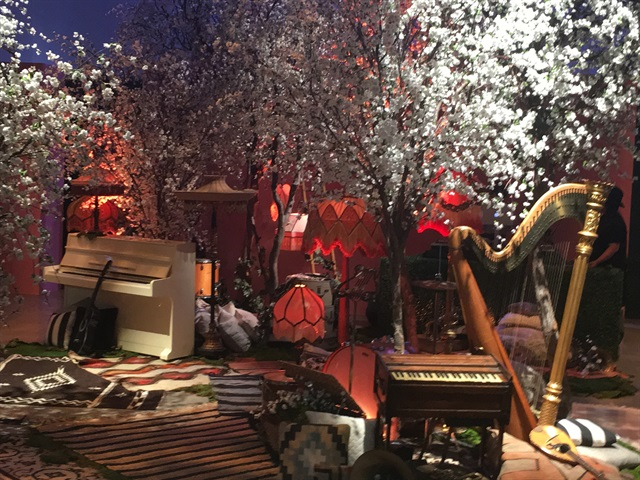 <p>The backdrop for the runway show was staged with falling petals, instruments, and had a loungy, boho feel</p>
