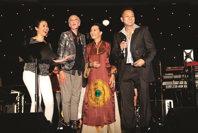 VietSALON managing editor Anh Tran, CND co-founder and style director Jan Arnold, and CND brand ambassador Kieu Chinh present Tan Nguyen with the trophy for his winning nail art mural.