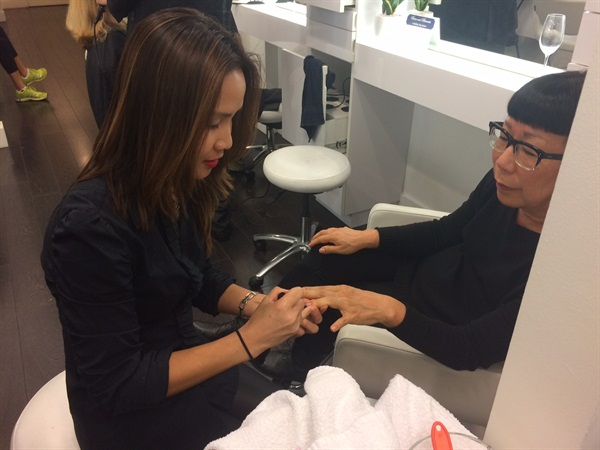 Manicurist Tammy Trung polishes up a partygoer's nails.