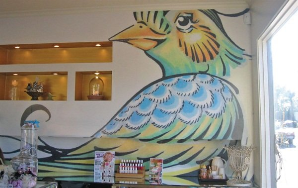 <p>The back wall of Lulu's has the easily recognizable bird illustration that adorns the salon's media materials.</p>