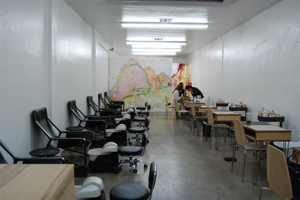 Six pedicure chairs and six manicure tables lead to an art instillation created byHeather Lembcke.