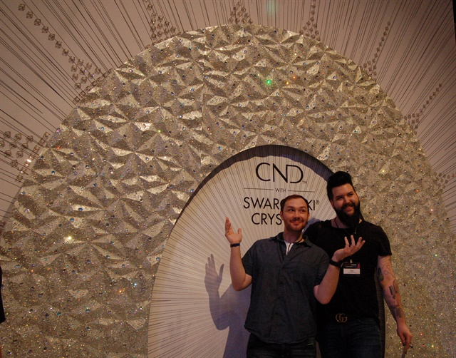<p>Braden Jahr and Nellie Neal pose in front of the crystal wall.</p>