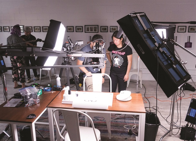 <p>Photographer Kim Pham amid the massive lights on-set with CND.</p>