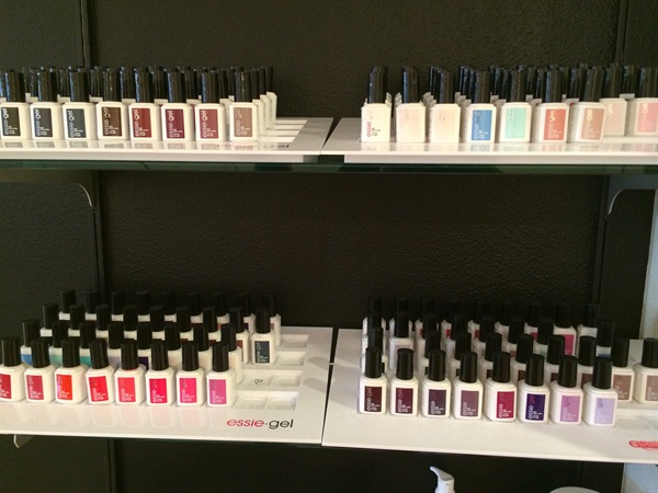 <p>Gel-polish lines a wall of the manicure area.</p>