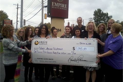 "<p>Students at Empire Beauty School in Framingham, Mass., present their adopted shelter ""Voices Against Violence"" with a check on Empire's National Day of Beauty.</p>"