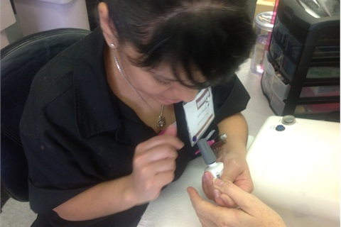 A student performs a gel manicure for one of the salon's clients.