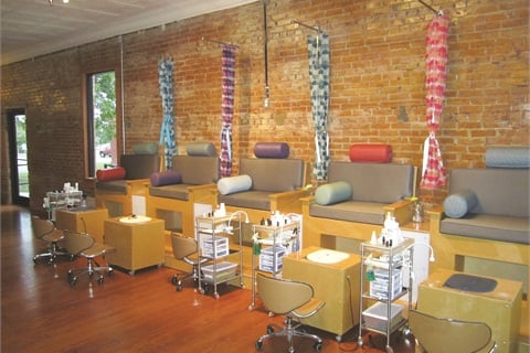 The simple yet modern elevated pedicure chairs that line the walls of SPAtaneity are separated by colorful curtain dividers for added privacy and feature color-popping pillows.