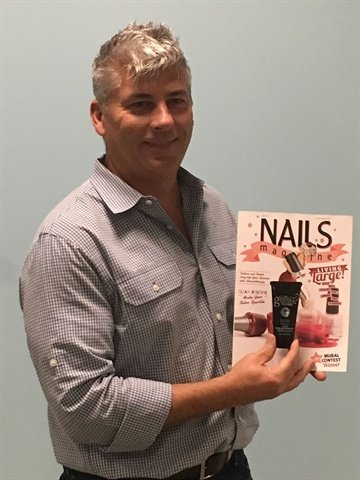 <p>Danny Haile poses with NAILS Magazine's March issue.</p>