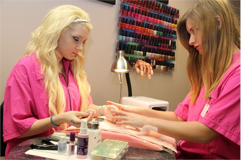 Students Shelby Johnson and Ariel Lack practice in the nail technology room.