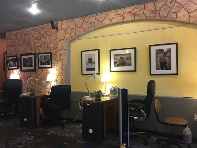 <p>Le's photos line the salon wall</p>