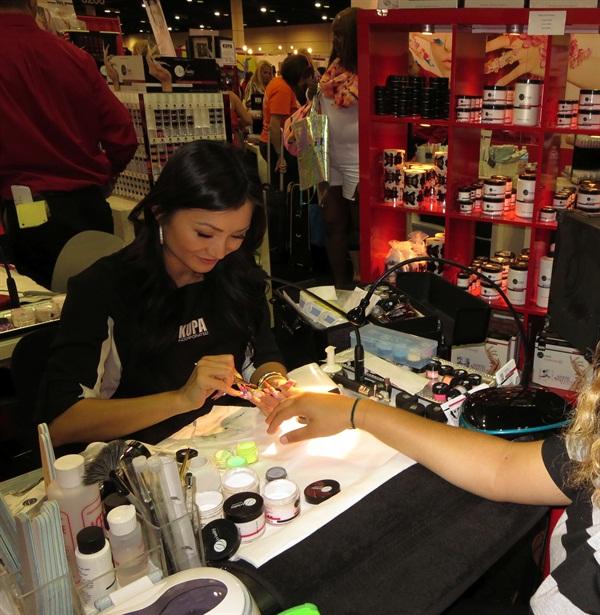 <p>A Kupa nail tech demonstrates at Premiere Orlando 2014.</p>