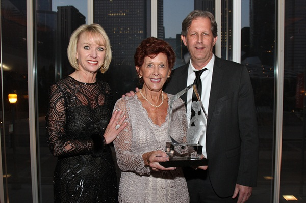 <p>Beauty Changes Lives president Lynelle Lynch presents the Legacy Award honoring Leo Passage to his wife Lenie and his son Robert Passage.</p>