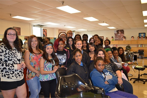 These students (comprised of about 10% nail students and 90% cosmetology students) pose with salon owner and school advisory committee member Maisie Dunbar (tall woman in the back row) during Dunbar's class visit.
