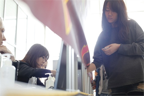 <p>Min Bang Kyung quickly scans the nails on a model. Judges had 10 seconds to judge one aspect of the nail</p>
