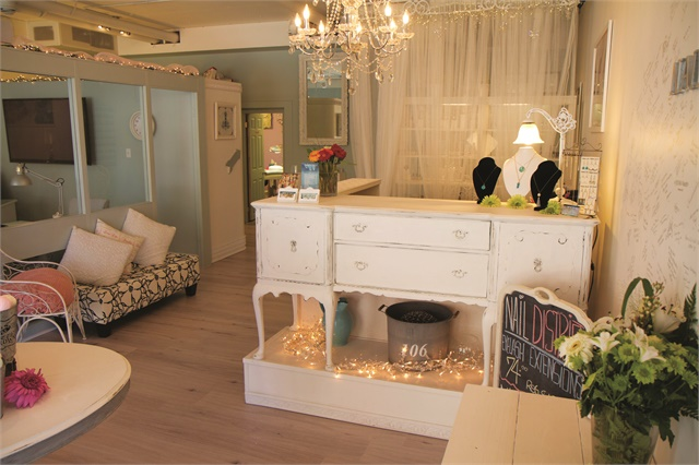 Nail District welcomes clients with a sparkling chandelier that illuminates a very clean and pale interior. A refurbished dresser perched on a raised base makes the perfect front counter.