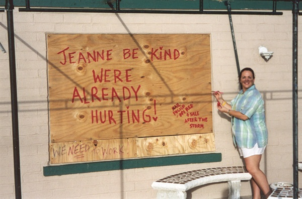 "<p>In the 45 MPH winds, I painted the plywood boarding up the salon using my OPI Red nail polish and my acrylic brush. I wrote, ""Jeanne be kind. We're already hurting,"" then below wrote, ""Painted with OPI Red polish, available after the storm!""</p>"