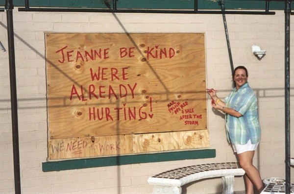"""<p>In the 45 MPH winds, I painted the plywood boarding up the salon using my OPI Red nail polish and my acrylic brush. I wrote, """"Jeanne be kind. We're already hurting,"""" then below wrote, """"Painted with OPI Red polish, available after the storm!""""</p>"""
