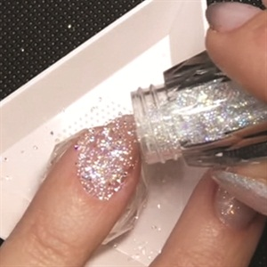 fe818a175d53 4. Sprinkle Crystal Pixie over the uncured layer of gel. Make sure to  rotate the nail to distribute the crystals evenly on the entire nail.