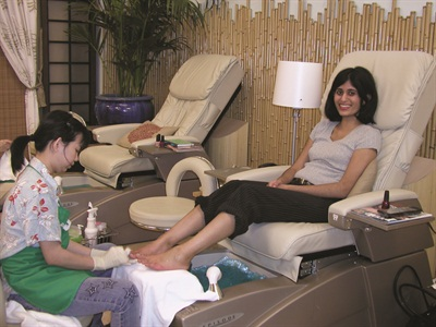 <p>Nail tech Lynn Vo gives me a pedicure. The salon's design features bamboo poles that reach halfway up the walls.</p>