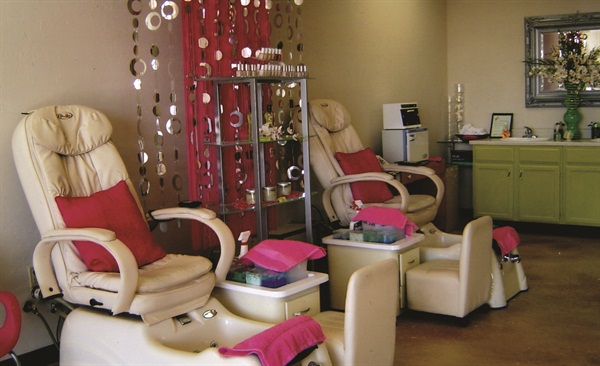 <p>A modern silver curtain made from chains of hollow circles dangles against the wall between pedicure stations.</p>