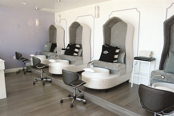 Four chic custom and cozy pipeless pedicure chairs are equipped with a subtle massage and heat feature and extra deep bowls. Peep the custom black glitter chairs nail techs use.