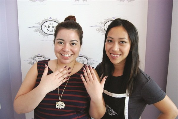 A step-and-repeat gracing The Painted Nail's logo is set up for clients to snap a quick picture after a service. That's me (left) and nail tech, Chi Phan.