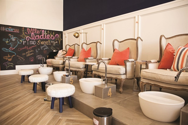 The feminine side of the salon's pedicure area features ivory chairs with coral pillows, and fluffy white stools for the nail techs.
