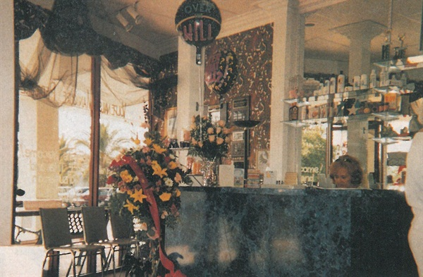 <p>Blue marbleized Formica and flowers, along with an ever-chaging display of knick-knacks and retail items, characterize Volpe Nails' decor.</p>