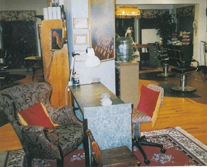 <p>Champion and Ventrone selected antique pieces to furnish the salon. The floral patterns in the window dressings, floor coverings, and upholstery lend warmth to functional furniture, such as the comfy client chair.