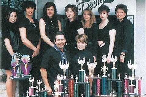 <p>It's not clear whether Tye Broughton has more staff members or competition trophies. She and husband/partner Glenn (seated, front) are proud of the fact that almsot all their nail technicians compete (from left to right, Christina Olsen, Tonia Waldron, Kayte Mihaljevich, Denise Shirk, Karen Ehrmantraut, Jehne Allbritton, and Cindy Gilman).</p>