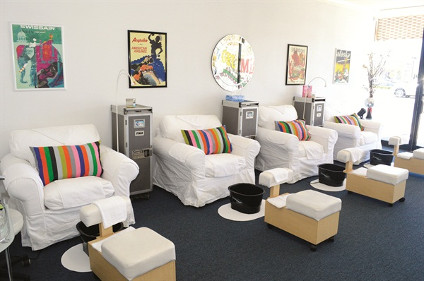 Vintage airline posters grace the walls behind comfortable pedicure chairs, Footsiebaths, and Vintage TWA flight carts.