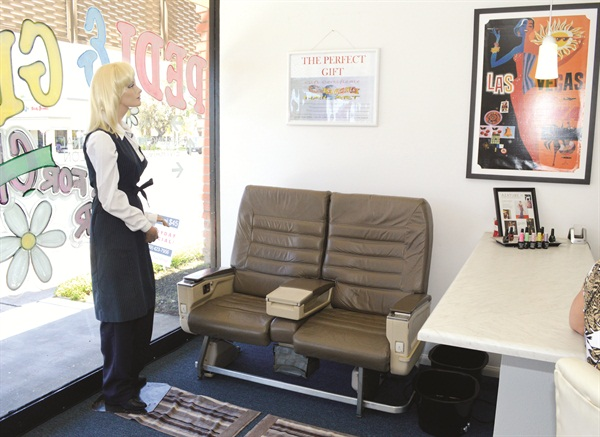 "<p>Flight attendant ""Betty"" oversees a second waiting area where clients can relax in two real first-class airplane seats.</p>"