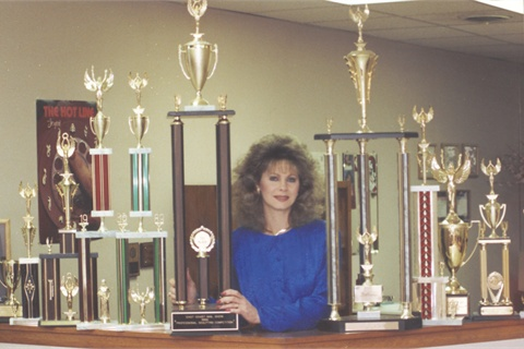 <p>Victoria with a collection of her competition trophies.</p>