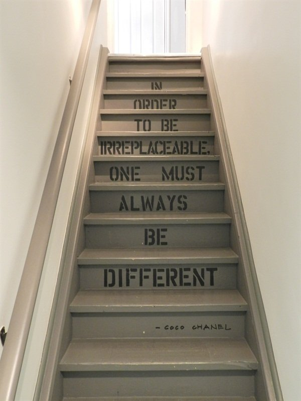 The staircase between the main level and the lower level displays a quote from Coco Chanel.