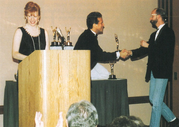 <p>Co-hosts Cyndy Drummey and Norm Freed congratulate Tom Nordstrom of Creative Nail Design.Nordstorm accepted the award for Educational Video, and gave particular thanks to his sister Jan Bragulla for her devotion to education.</p>