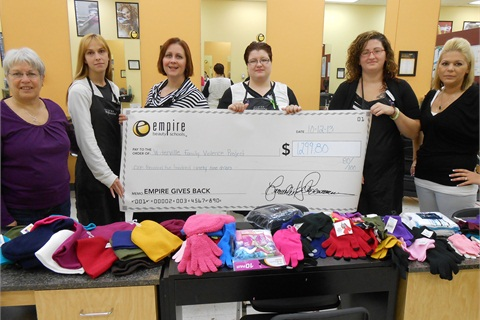 <p>Staff and students at Empire Beauty School in Waterville, Maine, take part in Empire's National Day of Beauty by presenting a local shelter a check along with donated winter clothes.</p>