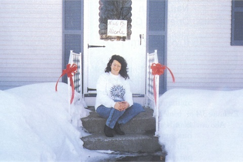 <p>Nicole Forest sits on her salon's dorrstep after having cleared out mounds of snow so clients could get through.</p>