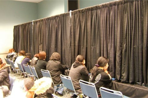 <p>During the judging phase, models place their hands under a curtain while the judges inspect each hand. Sometimes the judging process can take up to three to four hours for one category.</p>