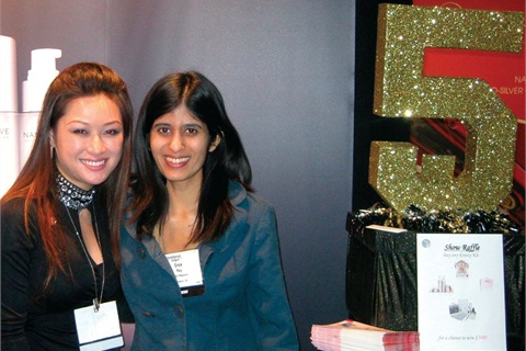 """<p>Entity educator Cyndi Van and managing editor Sree Roy can't resist a shot by the sparkly """"5"""" that graced Entity's trade show booth.</p>"""