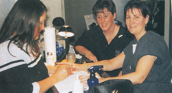 <p>Makeover contest winner Pat Shinn receives a manicure from Michelle Mason. Debbie Adams, who nominated her for the makeover, is by her side.</p>