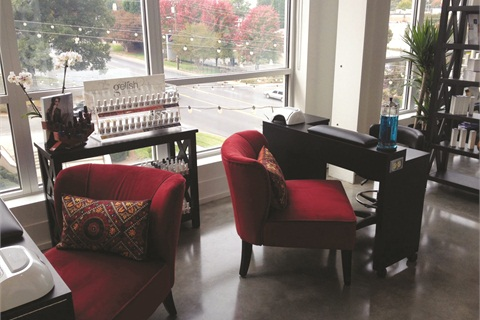 <p>Two nail techs work at this Charlotte medical spa that is beautifully adorned with charcoal and cranberry accents.</p>