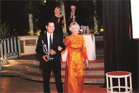 Advanced Beauty College's Tam Nguyen escorts Tippi Hedren offstage with her Legacy of Style Award.